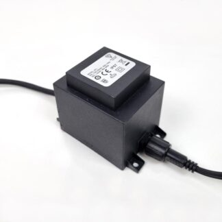 Close-up of a transformer, cuboid in shape. Label showing safety marks. Screw fit cable connectors. Lugs for wall mounting.